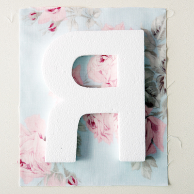 1) Cut a fabric square a few centimetres larger than your letter.