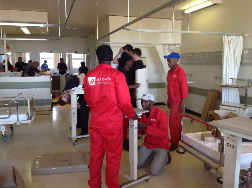 An Easylife Kitchens team hard at work replacing the worn panels on the beds and tables with brand new PG Bison boards.